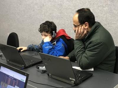 a student and parent on computers